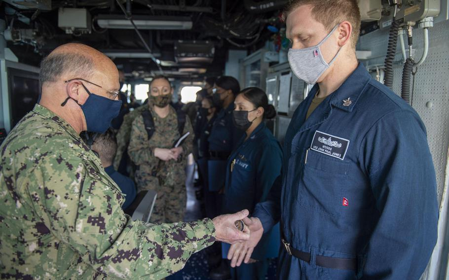 Adm. Mike Gilday, chief of naval operations, presents a challenge coin to operations specialist Petty Officer 1st Class Anthony Woods in the pilot house aboard the destroyer USS John Paul Jones, in the Persian Gulf, Jan. 13, 2021.