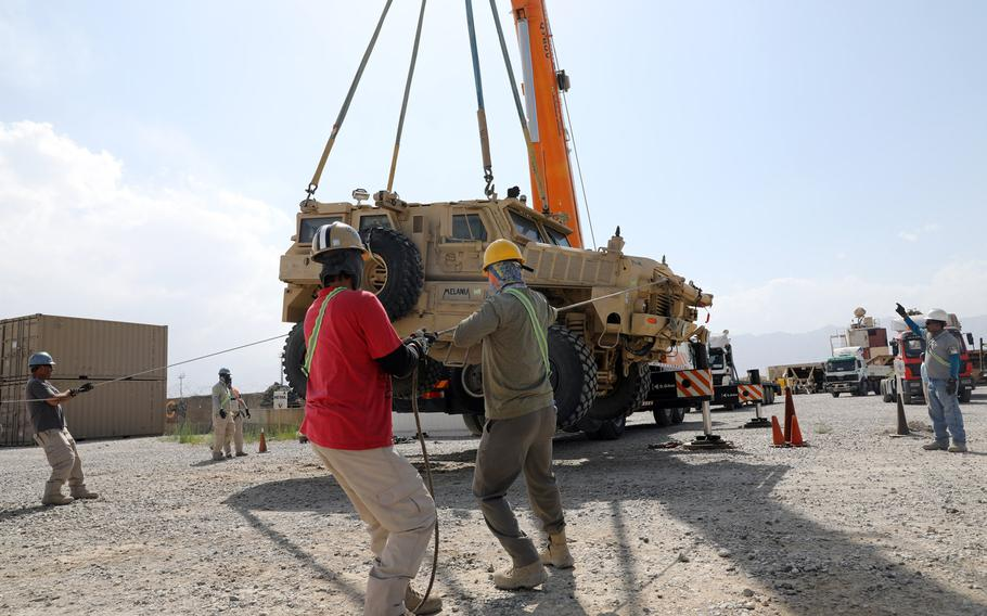 Civilian contractors prepare to load a Mine Resistant Ambush Protected vehicle on to a flatbed trailer at Bagram Airfield, Afghanistan, July 12, 2020. The U.S. has more than 18,000 contractors in Afghanistan and about 2,500 troops, an Army report said this week.