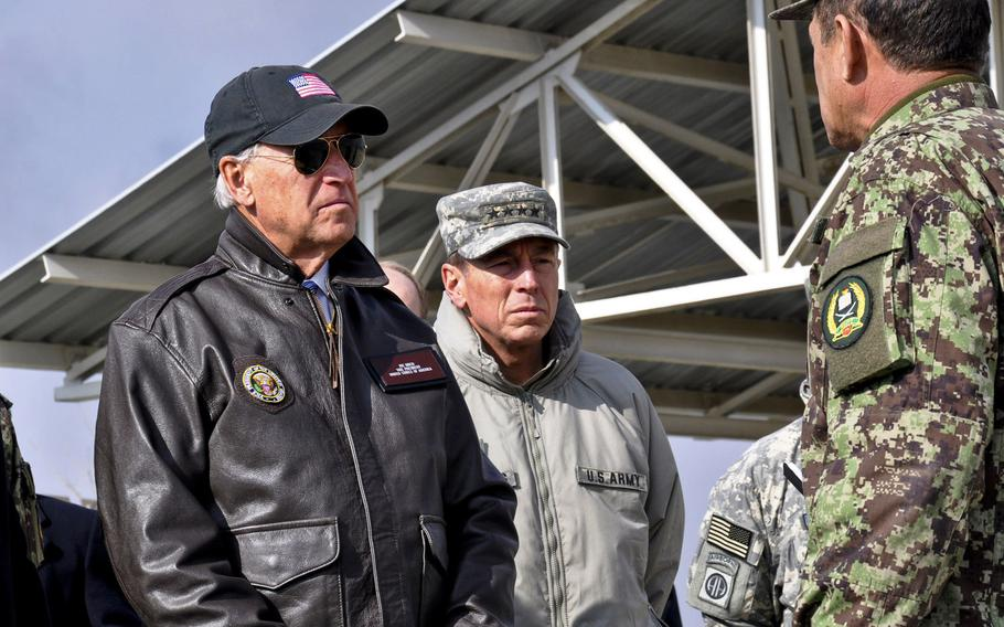 In a 2011 visit to Afghanistan, then-Vice President Joe Biden listens to Afghan Brig. Gen. Amlaqullah Patyani, commander of Kabul Military Training Center. In the center is Gen. David Petraeus, then the commander of the International Security Force. As president, Biden must determine whether to soon withdraw all U.S. troops from Afghanistan.