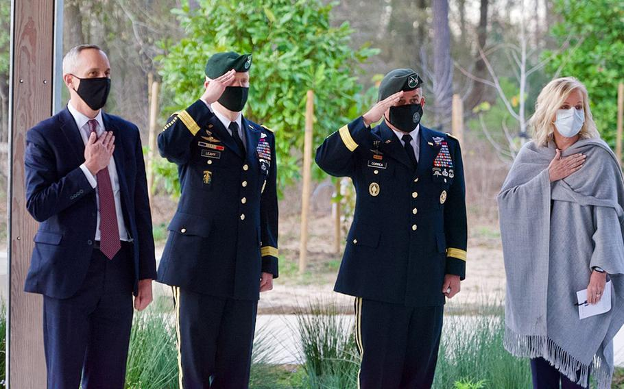 """Special Forces Brig. Gen. Kevin Leahy and Maj. Gen. Miguel Correa, flanked by unidentified civilians, salute during a ceremony to present a posthumous Silver Star Medal to Staff Sgt. James ''Jimmy"""" Moriarty's family in Houston on Wednesday, Jan. 27, 2021."""