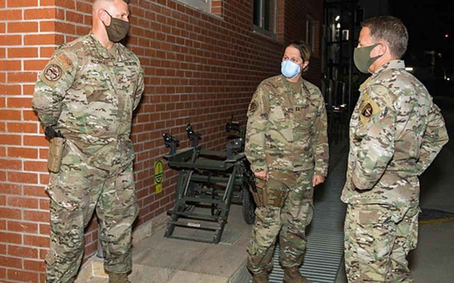 Air Force Master Sgt. Brandon Hockenbarger, left, briefs Gen. Scott Miller, commanding general of U.S. and coalition forces in Afghanistan, on efforts to combat a coronavirus outbreak at NATO Resolute Support Headquarters in Kabul, Afghanistan, sometime in 2020. In the center is Capt. Katie Coble. Hockenbarger, Coble and Capt. Kathleen Schurr were all awarded the Bronze Star for helping stem a coronavirus outbreak at the base.