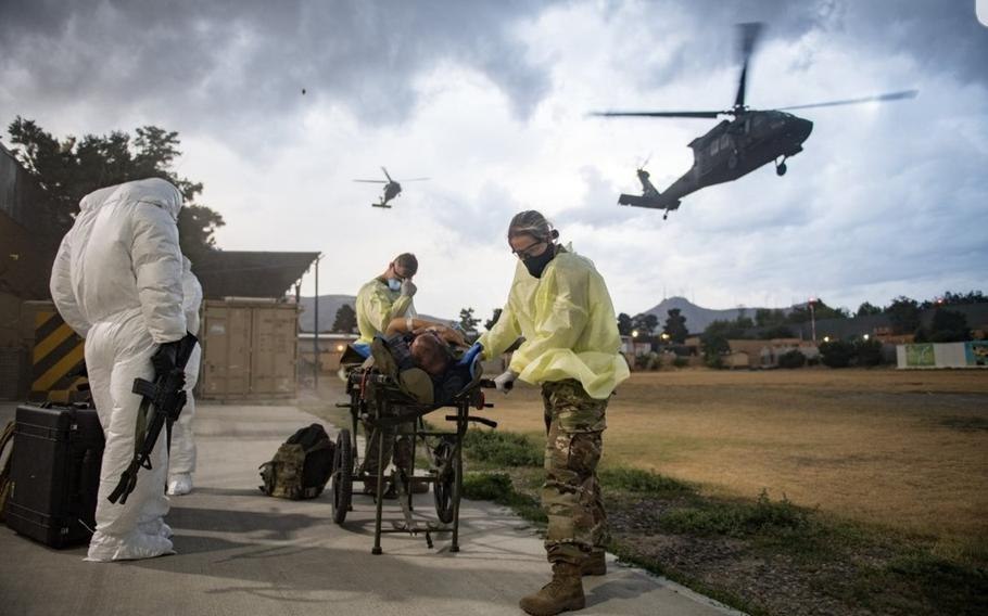 Troops at NATO Resolute Support Headquarters in Kabul, Afghanistan, assist a patient during an aeromedical evacuation due to COVID-19, in a photo taken in 2020.
