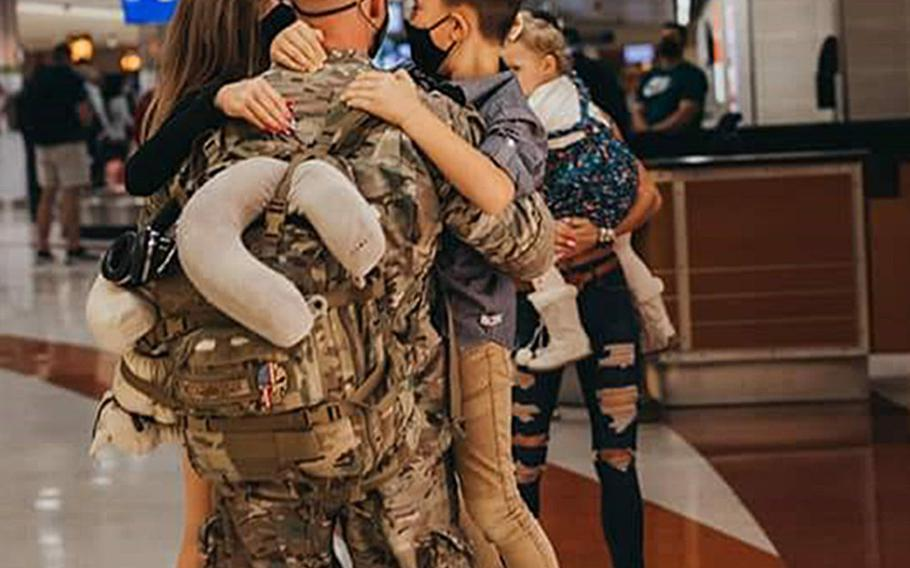 Air Force Master Sgt. Brandon Hockenbarger reunites with his wife and three children on Nov. 5, 2020, after a deployment fighting a coronavirus outbreak at NATO Resolute Support Headquarters in Kabul, Afghanistan.