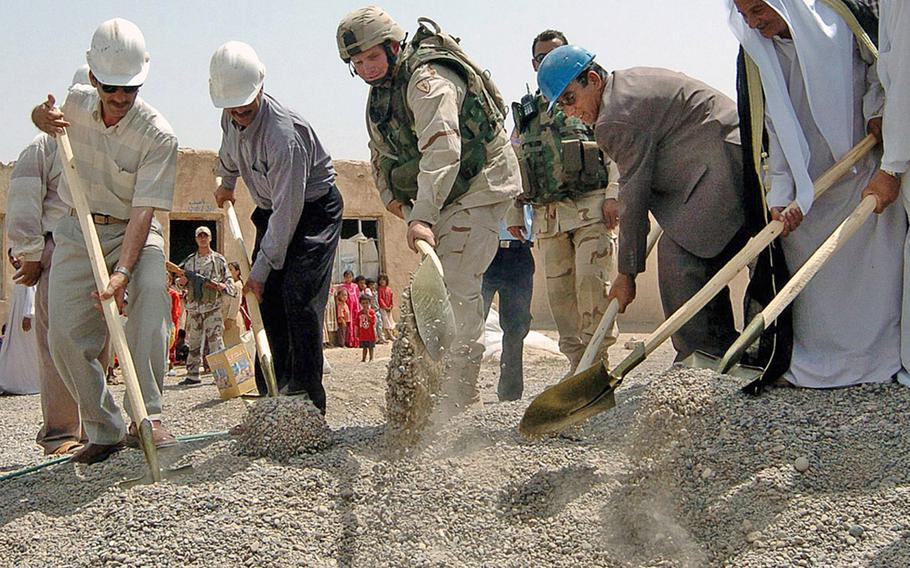 Capt. Whitney Campbell, center, commander of Battery C, Task Force 2-11 Field Artillery, participates in a ceremony in 2004 for the Kharabrud elementary school, which was funded through the Commander's Emergency Response Program. Lawmakers have directed the military to end multibillion-dollar program used in Afghanistan and Iraq.