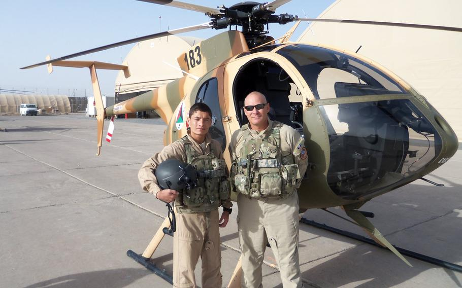 Mohammed Naiem Asadi poses with an instructor during flight training Aug. 28, 2012 in Afghanistan. Asadi, now an Afghan air force major, has reapplied for refuge in the United States while in hiding.