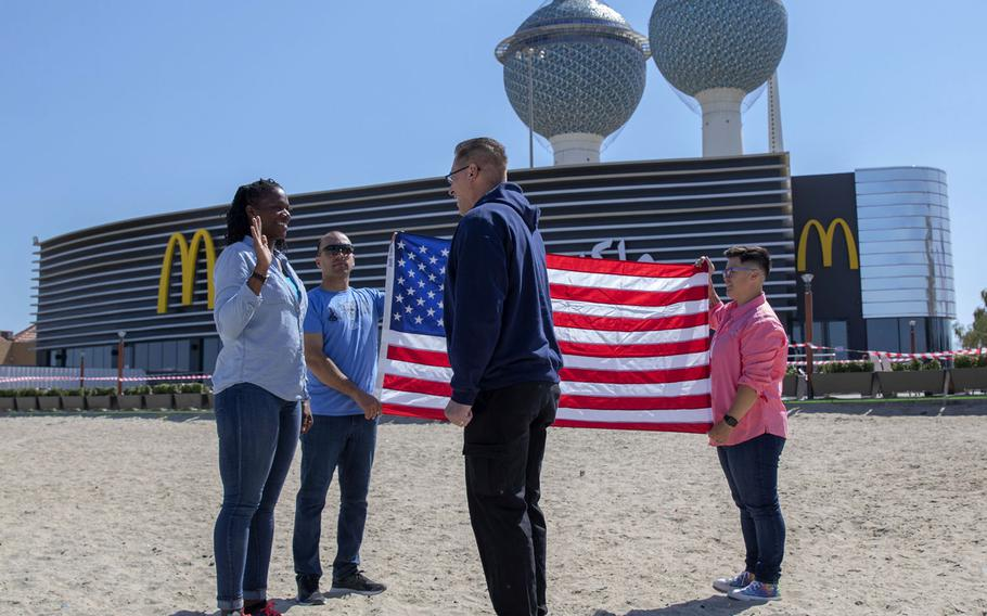 U.S. Army Staff Sgt. Nicole Atchley, with the 413th Combat Sustainment Support Battalion, affirms her reenlistment oath, led by Col. Christian Pajak, 413th CSSB commander, Feb. 26, 2021, in Kuwait City, Kuwait. Atchley chose to reenlist in front of a McDonald's because she makes a point of eating at one in every country she visits, the Army said.