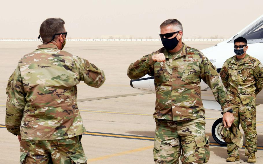Maj. Gen. Michael Koscheski, U.S. Air Forces Central deputy commander, gets ready to elbow-bump Brig. Gen. Evan Pettus, 378th Air Expeditionary Wing commander, as he arrives at Prince Sultan Air Base, Saudi Arabia, March 5, 2021. Military officials are urging continued vigilance against the coronavirus after a doctor said there was an uptick in infections in the region last month.