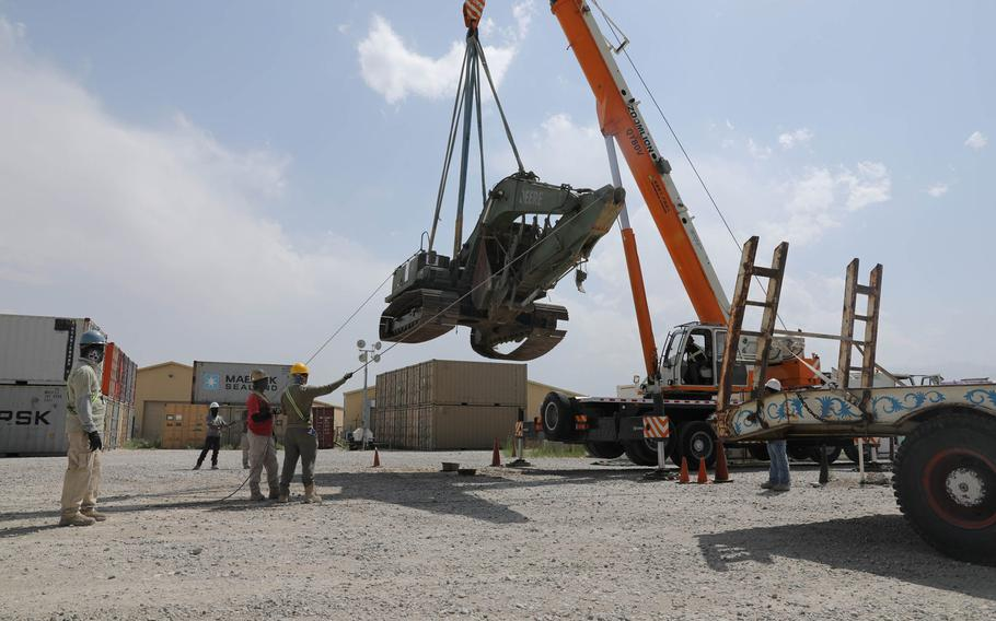 Contractors load an excavator during a retrograde cargo operation on Bagram Airfield, Afghanistan, in July 2020. U.S. troops must either begin a withdrawal soon to meet a May 1 deadline, or must extend their timeline to avoid a disorderly exit, U.S. defense officials and analysts said.
