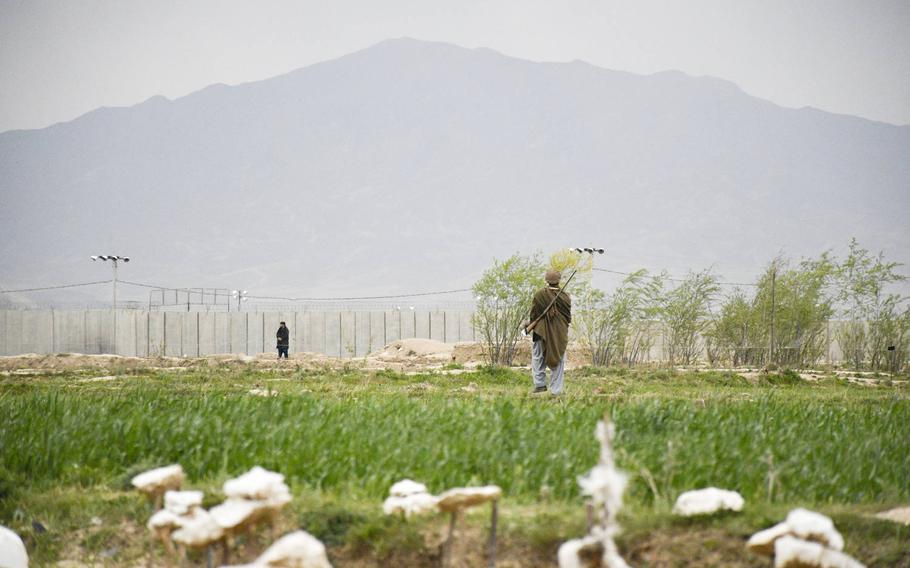 A hunter stalks birds near the outer walls of Bagram Airfield, the largest U.S. base in Afghanistan. The area outside the base has grown over the last 20 years, as workers from all over the country arrived to find jobs.