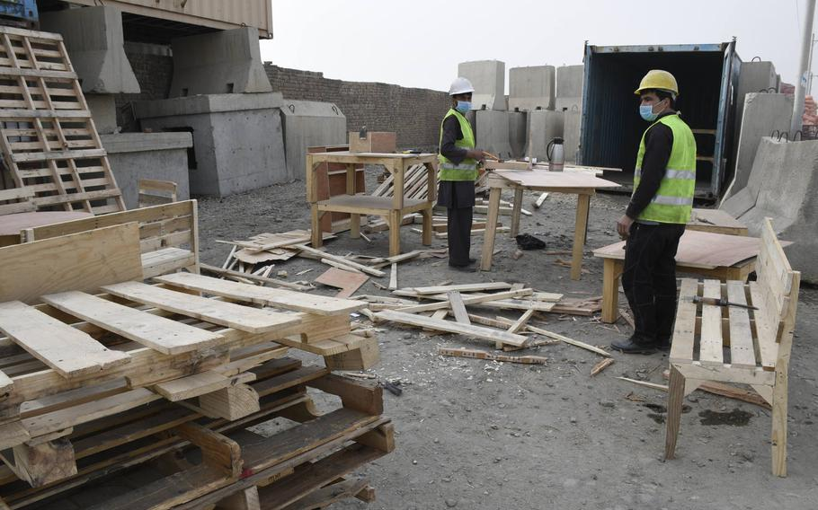 Carpenters in the village outside of Bagram Airfield pick through discarded wood pallets from the base to find the ones most suited to build tables, chairs and birdhouses. The area developed an economy over the last 20 years built on serving the needs of Americans and NATO allies.