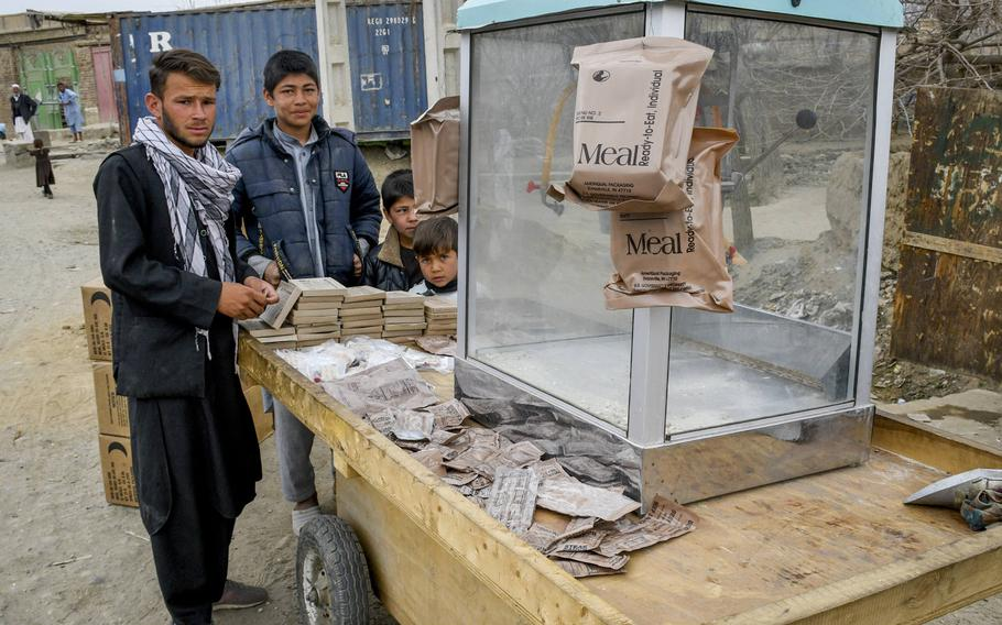 Children at a cart outside Bagram Airfield, Afghanistan sell items from Meals, Ready to Eat, the food rations issued to U.S. troops, in March 2021. Much of the economy nearby is dependent on what the base discards.