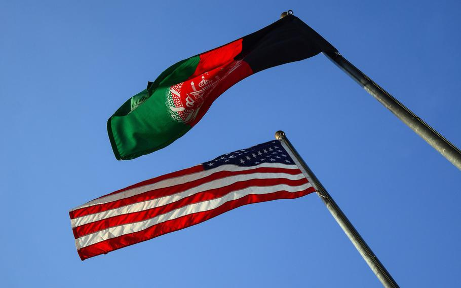 The American and Afghan flags fly over a base in Kabul, Afghanistan in 2019. Saed Ismail Amiri, who attempted to cheat Afghanistan's government out of more than $100 million, has pleaded guilty to fraud in a federal court in Los Angeles, the Justice Department said April 28, 2021.