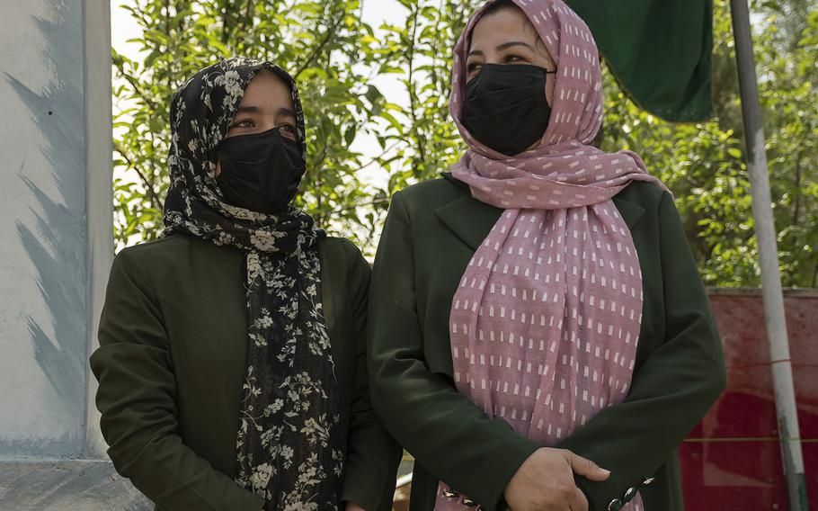 Sadiqa Halim, left, and Fatima Ravi watch students leaving a school in central Kabul on Sunday, May 2, 2021. Both women, who work at a school, said they were unhappy with the U.S. decision to withdraw from the country.