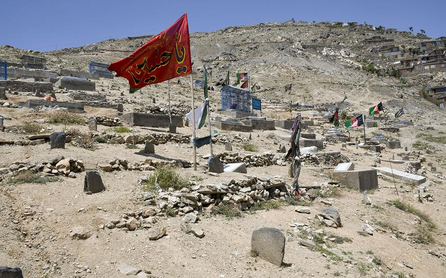 Flags fly over a cemetery in the Dasht-e-Barchi neighborhood, a majority Shiite district in the west part of Kabul, Afghanistan, where numerous funerals took place after an attack Saturday, May 8, 2021 on a school there.