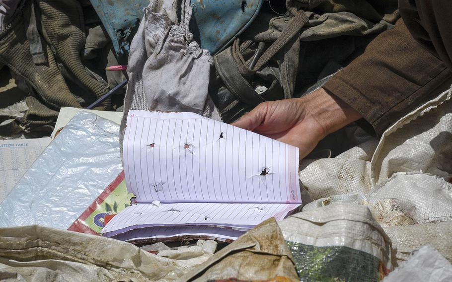 Locals examine items left behind after a deadly attack on the Syed Al-Shahda school in west Kabul, Afghanistan.