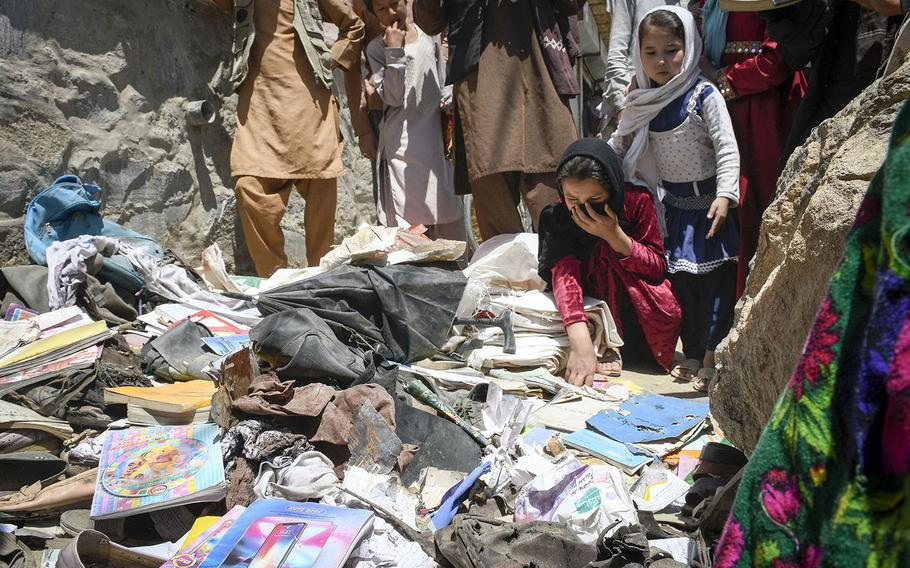 School children pick through items left behind after a deadly attack on the Syed Al-Shahda school in west Kabul, Afghanistan, including notebooks riddled with holes and discarded clothing. The Saturday attack left at least 50 dead and more than 100 wounded, a statement by the Afghan Interior Ministry said on Sunday, May 9, 2021.