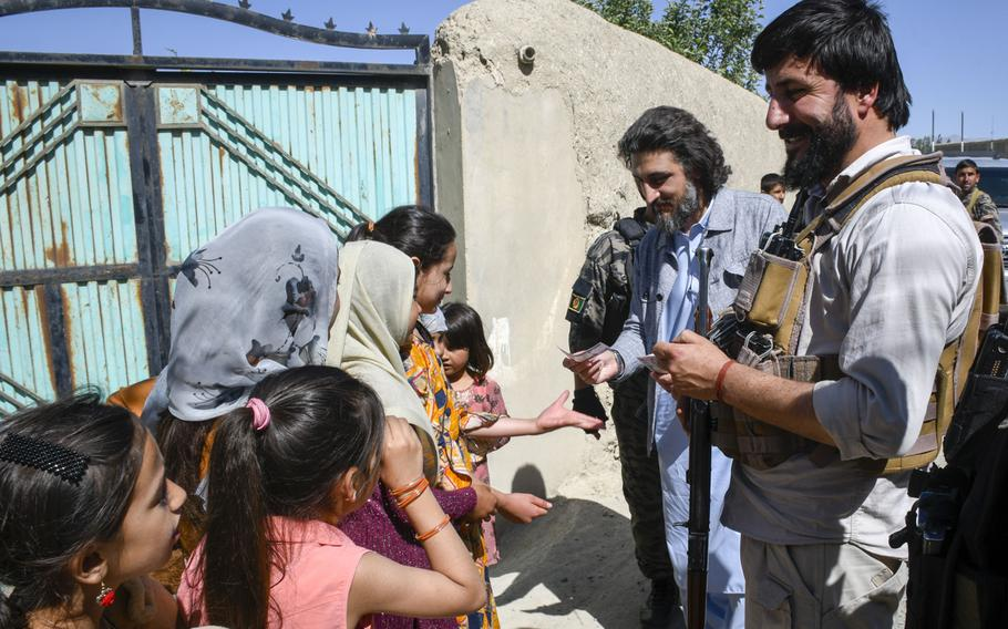Hussain Qadri, an adviser to the governor of the province of Logar in Afghanistan, gives 100 Afghani bills, worth about $1.29, to children in a Taliban-contested village during a cease-fire May 14, 2021. Qadri grew up in the village but has not been able to visit his childhood home in two years due to heavy fighting.