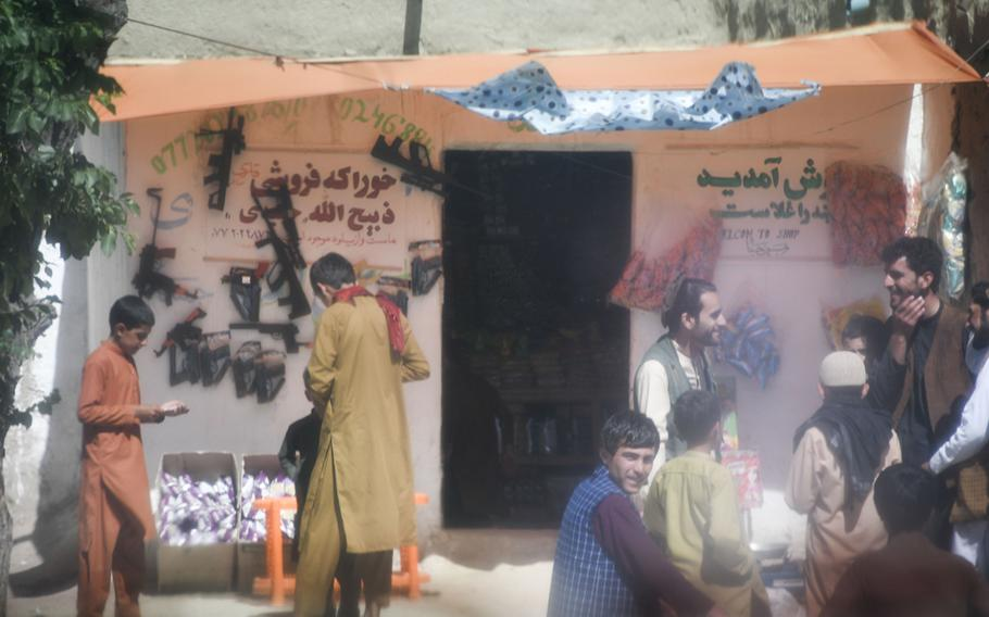 Residents of a Taliban-contested village in the province of Logar, Afghanistan, relax at a shop selling numerous toy weapons during a cease-fire May 14, 2021, in a photo taken through bullet-proof window.