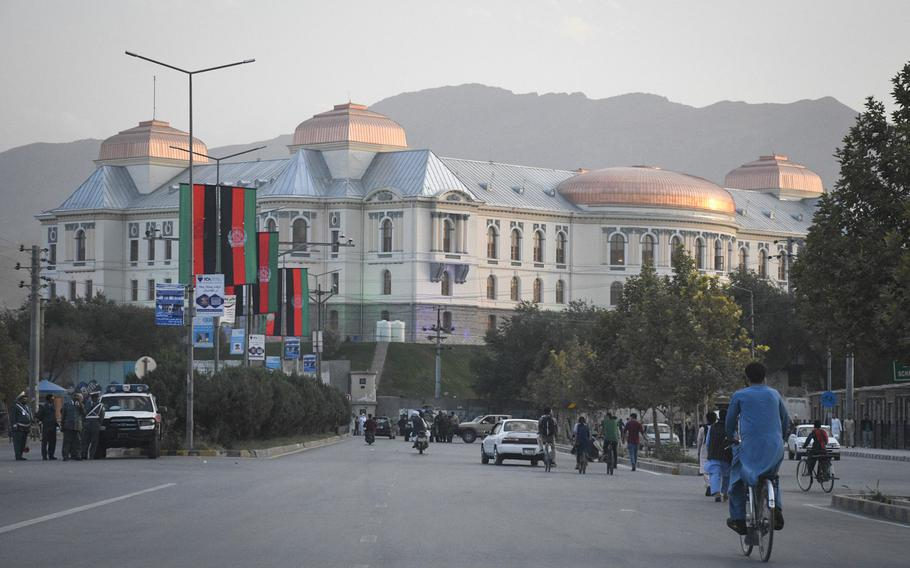 Afghans bike and drive past Darul Aman Palace in Kabul, Afghanistan prior to a celebration of the country's Independence Day on Aug. 18, 2020. The palace, once ravaged by years of war, has been restored and rehabilitated.