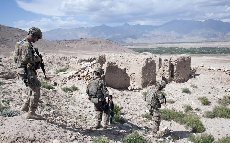 Airmen with the 455th Air Expeditionary Wing, Task Force Reaper, descend a hillside past an old earth building near Bagram Airfield in 2012.  Media reports indicate President Donald Trump will reduce the number of U.S. forces in Afghanistan to 2,500 by mid-January.