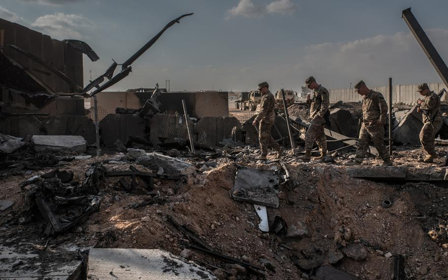U.S. officials stand near a crater caused by Iranian airstrikes inside al Asad Air Base near Anbar, Iraq, on Jan. 13, 2020.
