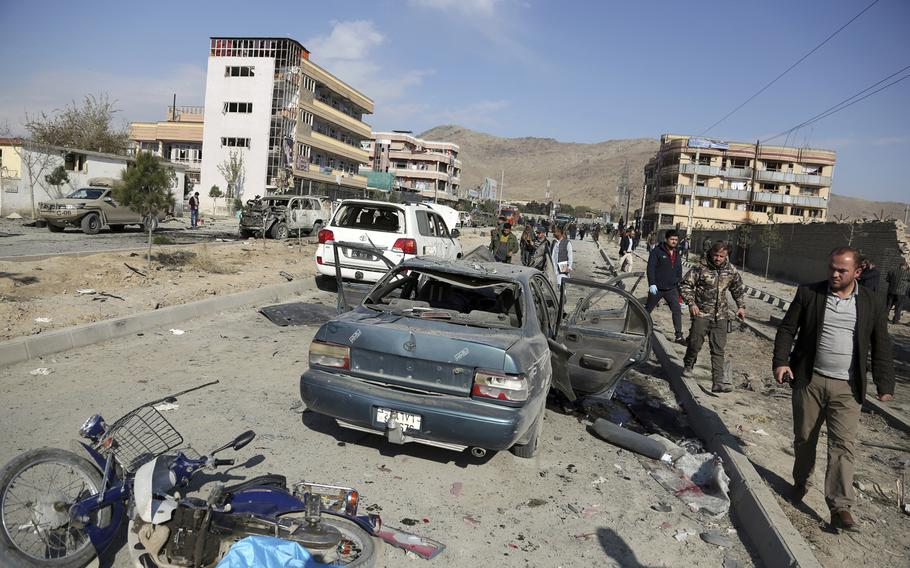 In this Wednesday, Nov. 13, 2019, file photo, Afghan security personnel gather at the site of a car bomb attack in Kabul, Afghanistan.