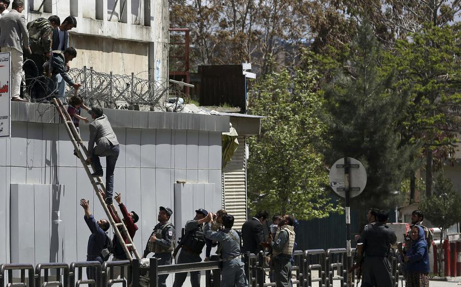 Afghan security personnel rescue men and children from the information and culture ministry after an attack near to the Telecommunication Ministry in Kabul, Afghanistan, Saturday, April 20, 2019.