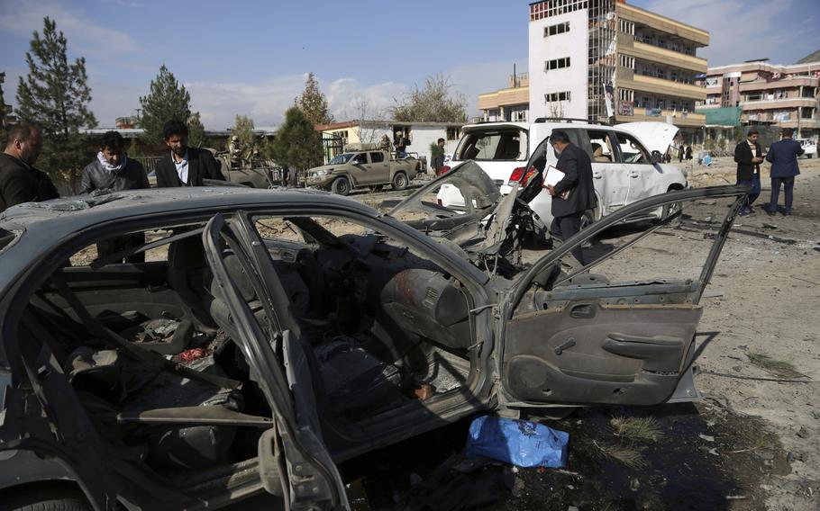 Local security personnel gather at the site of car bomb attack in Kabul, Afghanistan, Wednesday, Nov. 13, 2019. A car bomb detonated in the Afghan capital during Wednesday's morning commute, killing seven people and wounding at least 10, officials said.