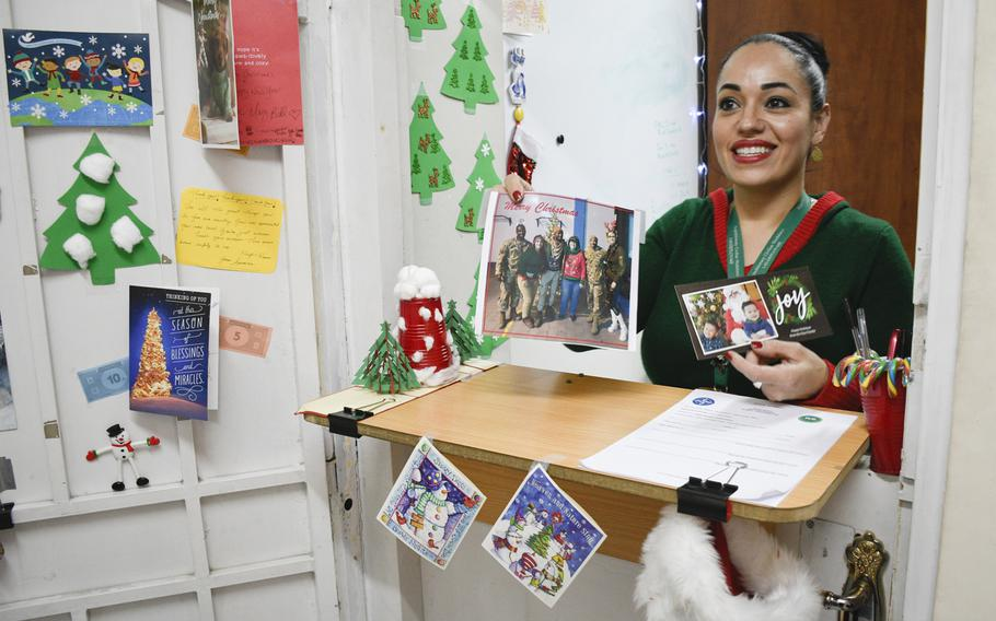 Rosa De La Paz, a Department of Defense civilian, holds up a photo of a recent ugly sweater contest held at the central NATO and international coalition base in Kabul, Afghanistan to celebrate Christmas of 2019.