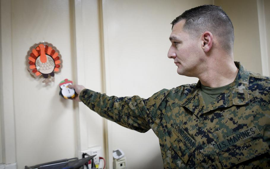 Capt. Christopher Countryman, a Marine deployed to the central NATO and international coalition base in Kabul, Afghanistan, puts up a decorative penguin on the walls of his office to celebrate Christmas of 2019.