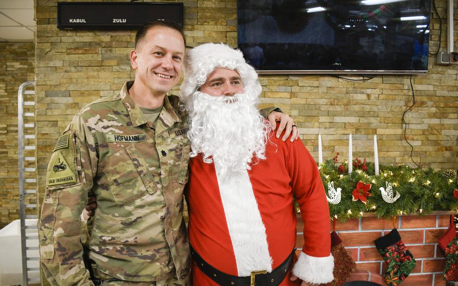A soldier deployed to the central NATO and international coalition base in Kabul, Afghanistan celebrates Christmas of 2019 by posing for a picture with a Santa in the base cafeteria.