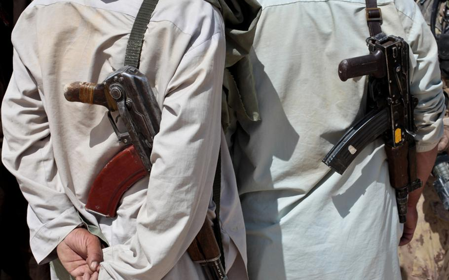 Villagers carry Kalashnikov rifles as they talk with U.S. and Canadian troops outside the village of Zormashor, in Dand district, Kandahar province, Afghanistan. With the U.S. and Afghan forces unable to reach many rural areas, they are turning increasingly to Afghan villagers to arm and protect themselves against the Taliban. June 27, 2010.
