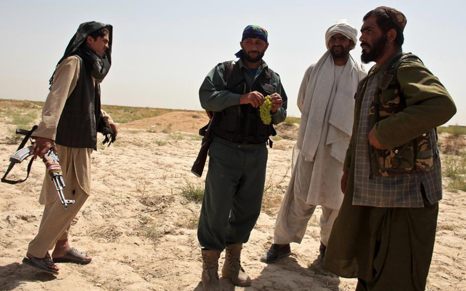 An Afghan policeman on patrol with U.S. and Canadian troops chats with three armed villagers outside Zormashor, in Dand district, Kandahar province, Afghanistan. With U.S. troops and Afghan forces unable to reach many rural areas, they are turning increasingly to village groups to arm and protect themselves against the Taliban. June 27, 2010.