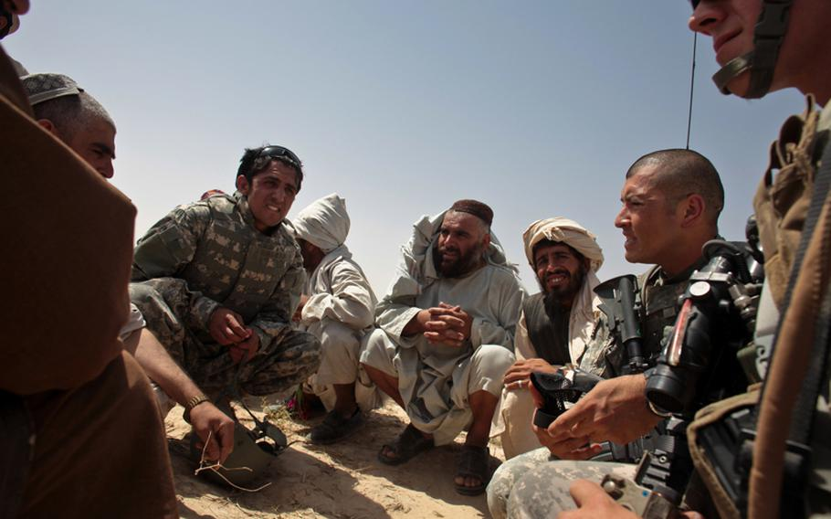 Staff Sgt. Julio Jurado, right, and other soldiers talk with armed men outside the village of Zormashor, in Dand district, Kandahar province, Afghanistan. With U.S. and Afghan government forces unable to reach many rural areas, they are turning increasingly to village groups to arm and protect themselves. June 27, 2010.
