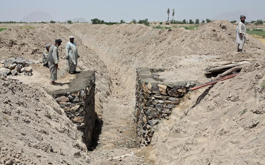 """Villagers stand beside a new bridge and irrigation canal being dug using U.S. and Canadian development money near the village of Zormashor, in Dand district, Kandahar province, Afghanistan. June 27, 2010. U.S. troops in the district can't patrol in the village 24 hours a day, so they rely on an armed """"village security team"""" to guard the project against Taliban attack. June 27, 2010."""