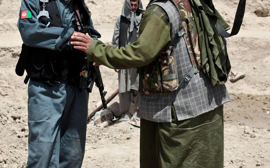 An Afghan policeman chats with an armed man outside the village of Zormashor, in Dand district, Kandahar province, Afghanistan. With U.S. and Afghan government forces unable to reach many rural areas, they are turning increasingly to village groups to arm and protect themselves. June 27, 2010.