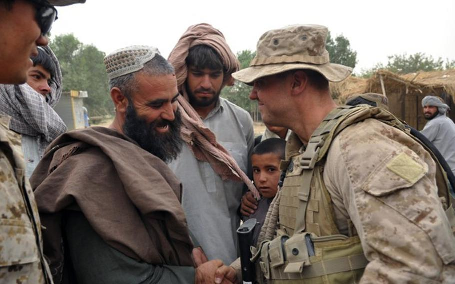 Gunnery Sgt. Brandon Dickinson, known to local residents as Gunny D, greets a villager whose family was killed during the initial offensive into Marjah but who has nevertheless befriended the Americans.