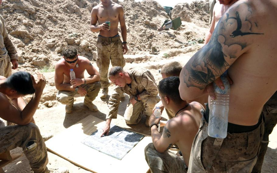 Cpl. Chad Wilson debriefs his squad following a firefight with insurgents in Marjah District on June 20. Wilson said the insurgents fired from buildings believed to have IEDs planted in front of them.