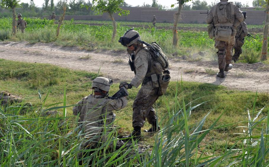 A Marine helps a comrade up the steep side of a canal ditch during an operation in search of an IED cache in Marjah District on June 25.