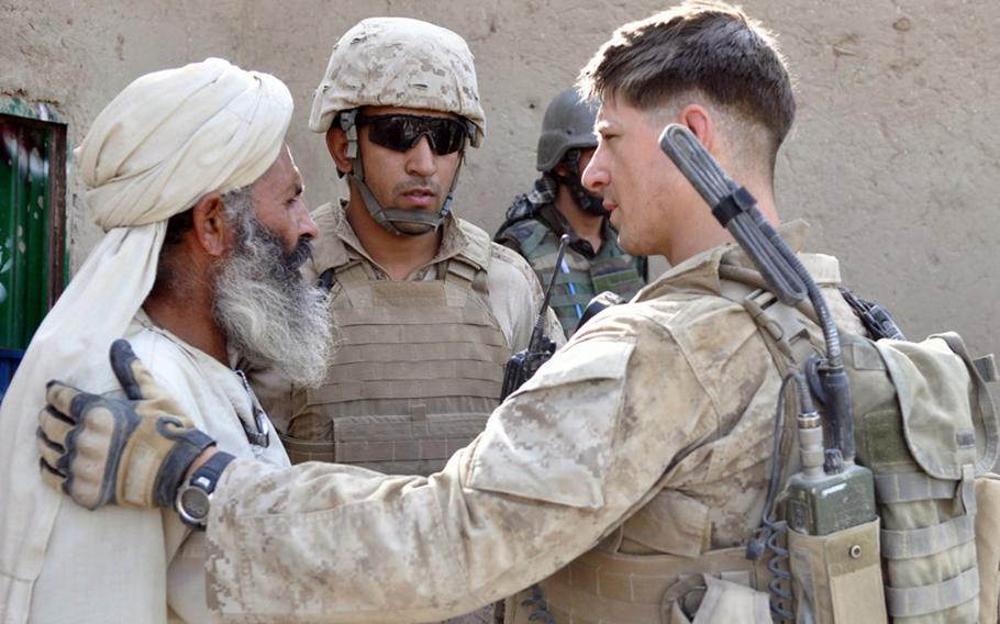 Marine 1st Lt. Dave Emison, 25, who leads the 2nd Platoon, talks with a homeowner during the search of his compound in Marjah District on June 25.