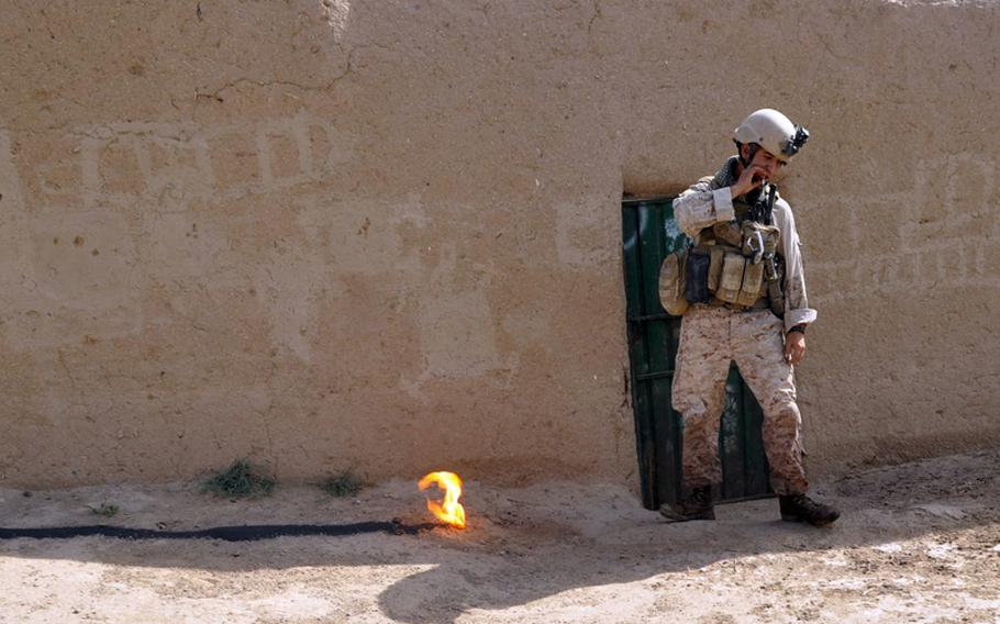 A Marine explosives technician drags off the cigarette he just lit with the fire he set to burn off gunpowder found buried inside a suspicious compound in Marjah District on June 25.