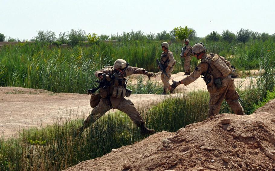 A Marine offers a hand to a comrade leaping an irrigation ditch during an operation in search of an IED cache in Marjah District on June 25.