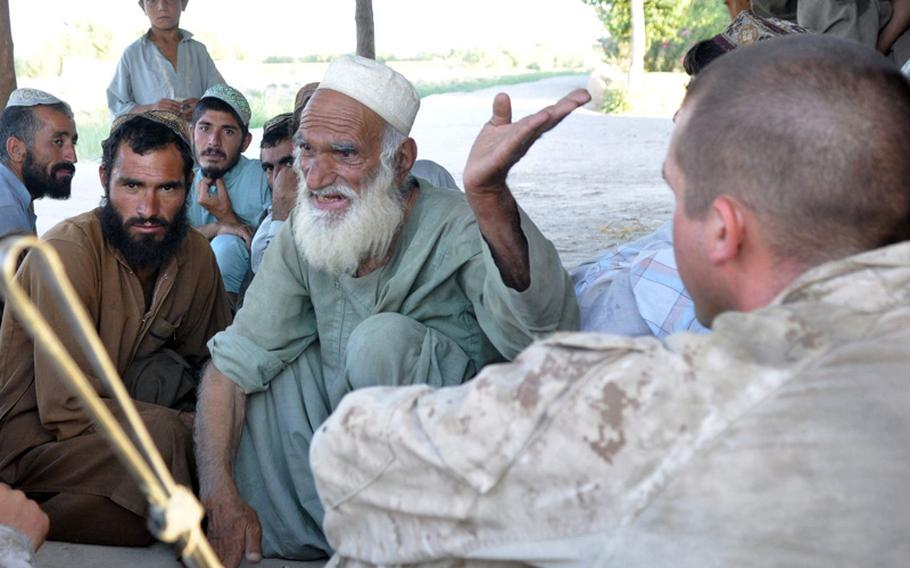 Marine 1st Lt. Christopher Young, right, listens as an old man describes the problems of his community in Marjah on June 18. Young was trying to convince the elders to give their young men arms to help fight off insurgents.