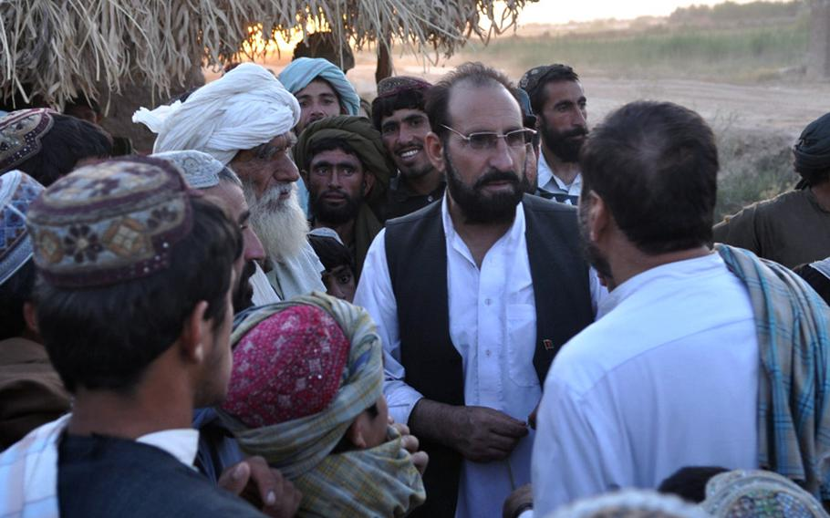 Marjah District Governor Haji Zahir talks to people at dusk on June 18, urging them to organize neighborhood watch programs to fight off the Taliban.
