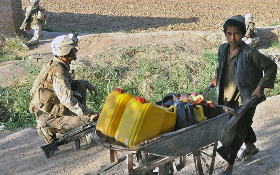 An Afghan boy pushes a wheelbarrow home from the field past a Marine from A Company, 1st Battalion, 6th Marines in Marjah District on June 19. Firefights and IEDs in the area are frequent.