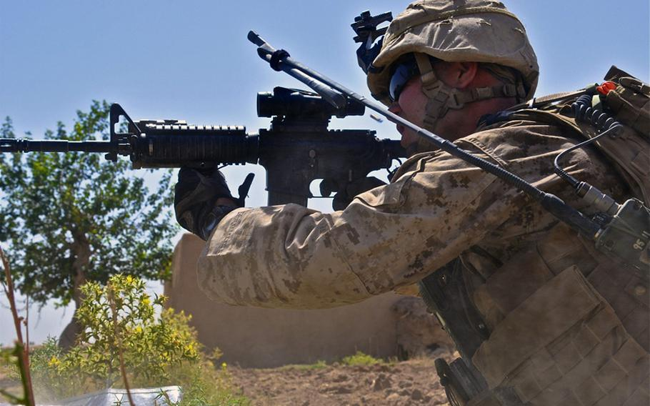 Cpl. Chad Wilson, a Marine squad leader, lets off a burst of rifle fire during a fight with insurgents in Marjah on June 20. Wilson said the insurgents were trying to lure the Marines to two buildings across an open field that were known to have IEDs set in front of them.