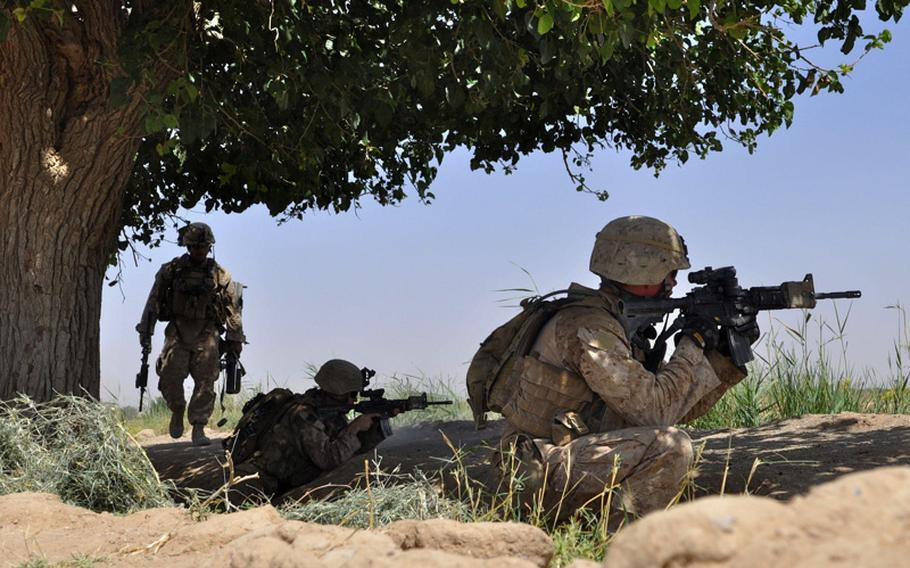 A Marine artilleryman walks to position during a gunfight with insurgents in Marjah on June 20. The insurgents fired across an open field from two buildings that Marines said were known IED locations.