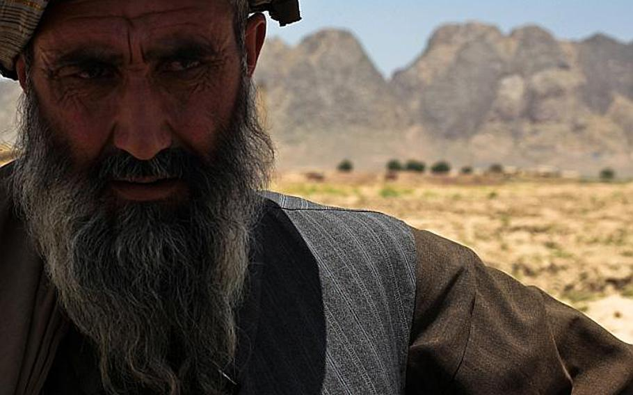 A man listens as U.S. troops with 1st Squadron, 71st Cavalry Regiment question him at a traffic checkpoint in Dand district, Kandahar province, Afghanistan. June 18, 2010.