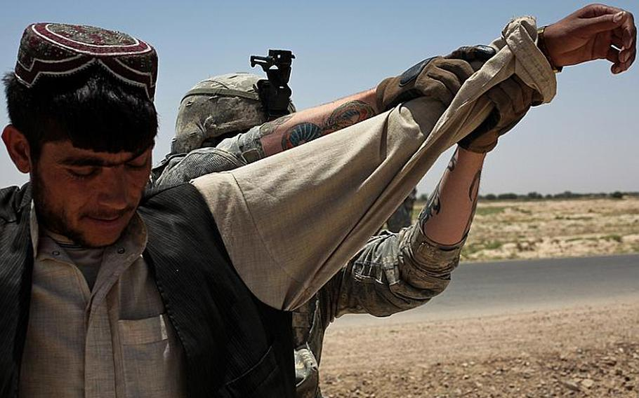 A soldier with 1st Squadron, 71st Cavalry Regiment searches a man at a traffic checkpoint in Dand district, Kandahar province, Afghanistan. June 18, 2010.