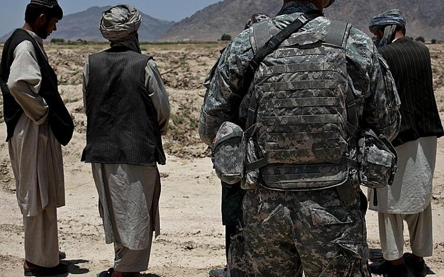 Pfc. Jesse Zurcher, of 1st Squadron, 71st Cavalry Regiment, stands guard over a group of Afghan men at a traffic checkpoint in Dand district, Kandahar province, Afghanistan. June 18, 2010.